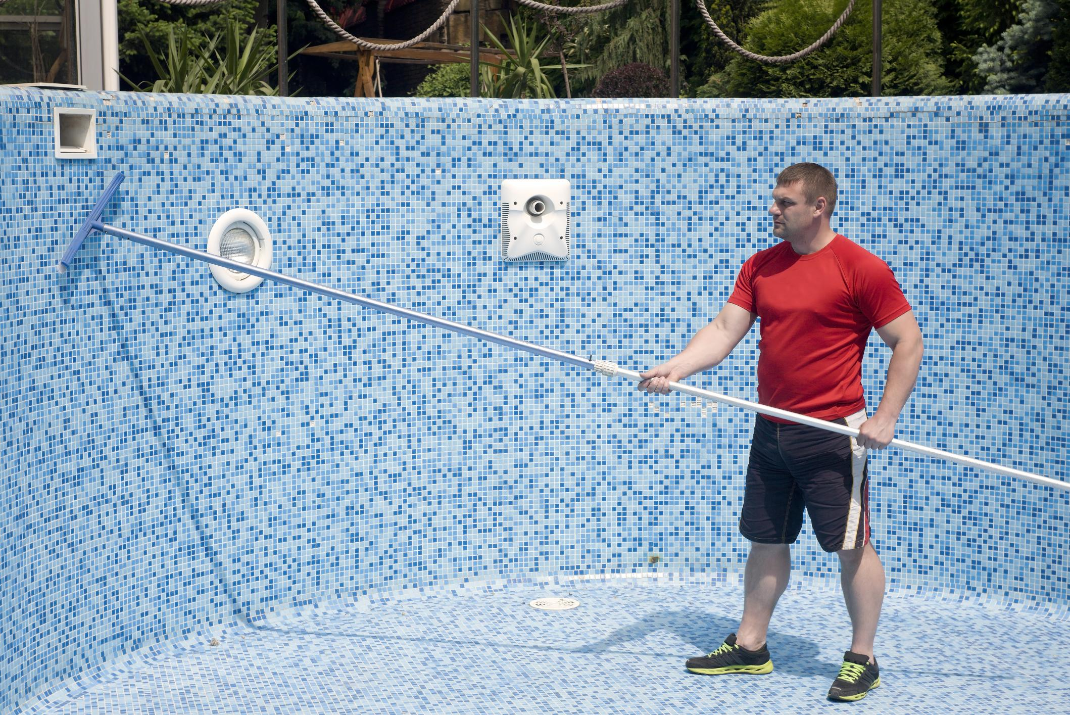 man cleaning tiles of an empty pool