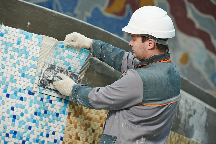 man applying pool tiles