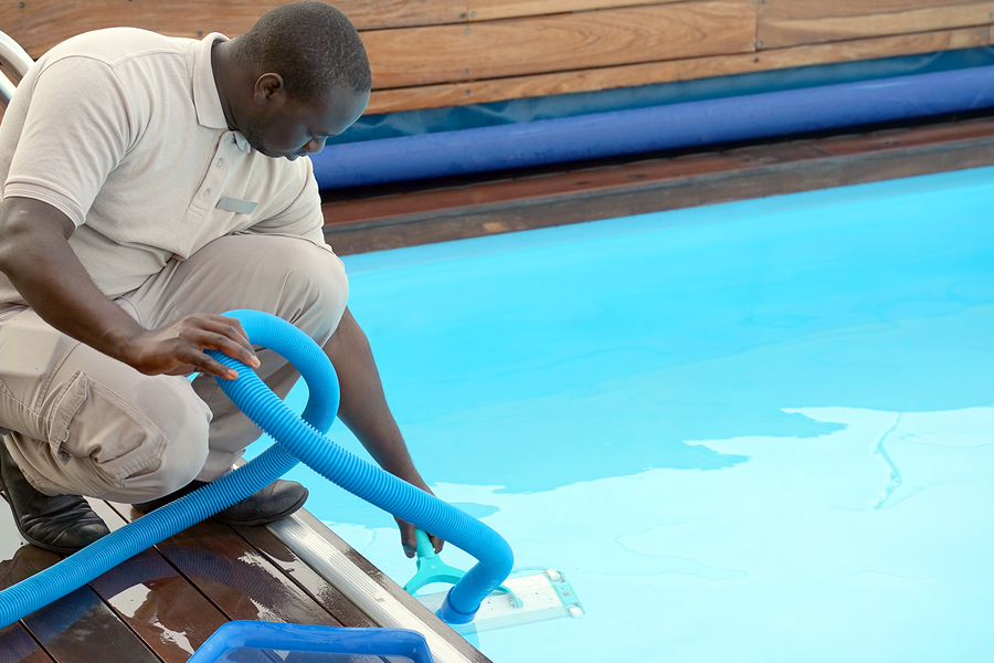 man using a pool vacuum